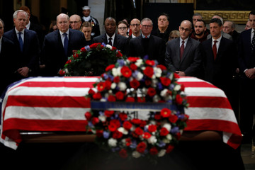 Former personal aides pay their respects at the casket of former U.S. President George H.W. Bush as it lies in state inside the U.S. Capitol Rotunda on Capitol Hill in Washington
