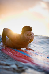 Male surfer prepares to push up into a standing position as a wave pushes his surfboard forward.
