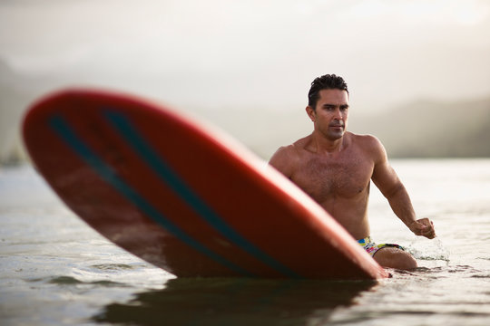 Male surfer sits on the end of his board in a calm sea.