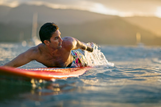 Male surfer lies on his board,  looks over his shoulder and paddles in anticipation of a coming wave.