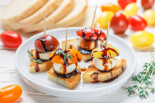 Bread toast with tomato cherry, mozzarella cheese, thyme and balsamic glaze on white wooden background. Canape. bruschetta. Gourmet snack. Selective focus