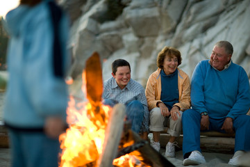 Mature couple and their teenage grandson sitting around a bonfire on a beach.