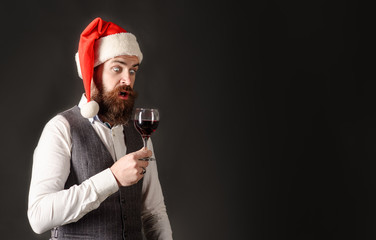 Santa man tasting glass of wine. Winetasting and degustation concept. New year party. Surprised man in Santa hat drinking red wine. Sommelier tasting red wine. Man in waistcoat drink glass of red wine