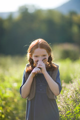 Portrait of a young girl smelling lavender while in a field.