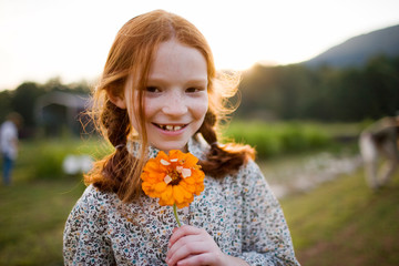 Portrait of a smiling young girl holding a flower.