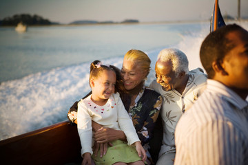 Mature adult couple sitting with their young granddaughter while on a boat.