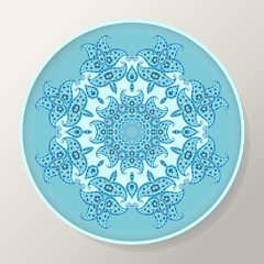 Decorative round plate with blue ornamental mandala from floral elements.