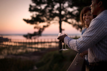 Laughing couple toasting wine glasses on a balcony at sunset.