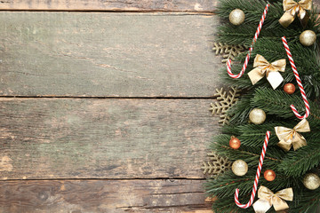 Christmas fir tree branches with decorations and candy canes on grey wooden table