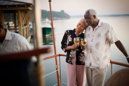Mature adult woman resting her head on the shoulder of her husband while holding wine glasses on a deck.