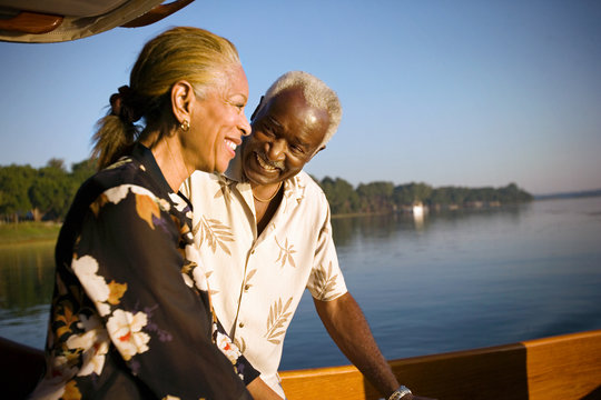Mature adult couple standing on a boat at sunset.
