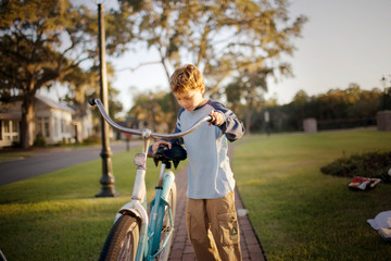 Boy with a bicycle along a brick path outside.
