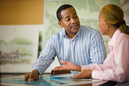 Mid-adult businessman discussing work with a mature female colleague.