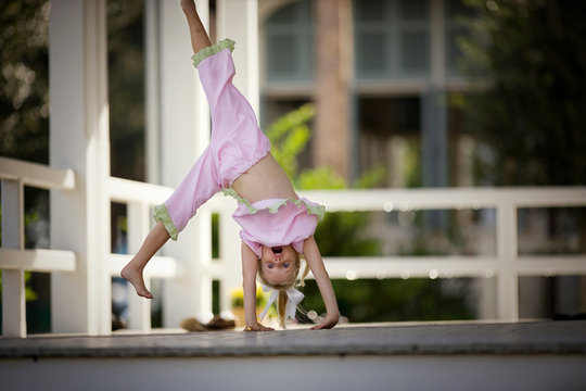 Portrait of a young girl doing a cartwheel.