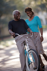 Smiling senior man sitting on a bicycle next to his mid-adult daughter.
