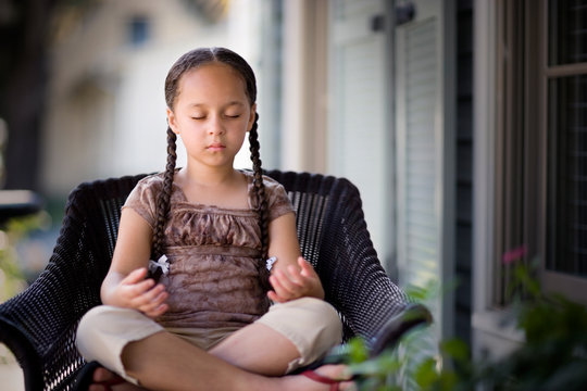 Young girl meditating on a chair.