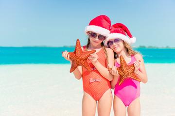 Adorable little girls on Christmas holidays on the beach