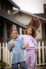 Young boy and his young sister playing on a suburban street.