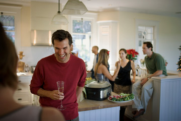 Laughing young man holding a champagne flute while inside a kitchen with friends.