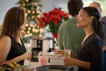 Two smiling mid-adult businesswomen holding champagne flutes at a Christmas party.