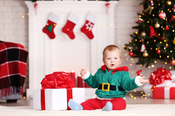 Little boy in christmas costume sitting on floor with gift box