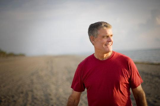 Mature adult man standing on a beach.