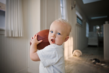 Young male toddler holding a rugby ball