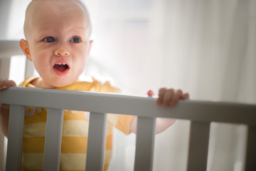 Toddler standing in a cot in a nursery room.