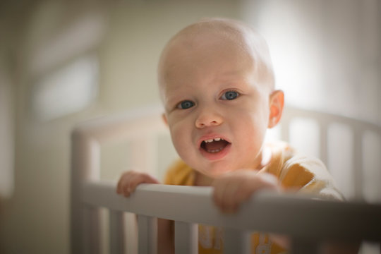 Portrait of a toddler standing in a cot in a nursery room.