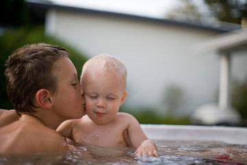 Boy kissing baby brother in swimming pool
