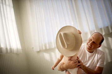 Mature man watching his baby son playing with a hat.