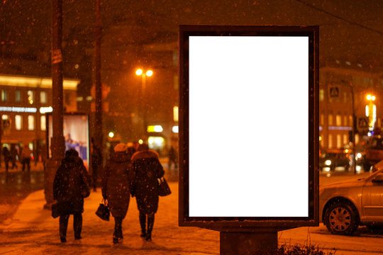 city outdoor billboard mockups place for ads winter city with snow going. Glows in the darkness of the night city.