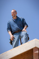 Smiling male builder standing on the roof of an incomplete house.
