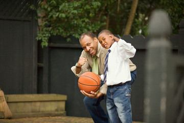 Portrait of a mid-adult man holding a basketball  with his young son.