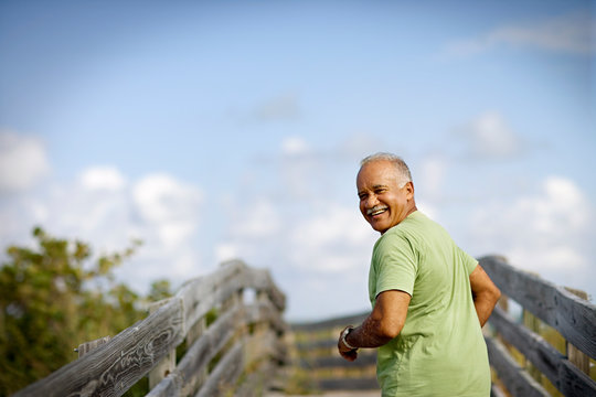 Portrait of a mature adult man smiling as he runs along a wooden beach pathway.