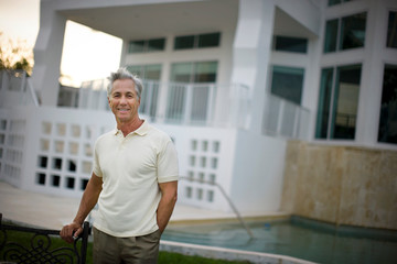 Mature man standing by swimming pool outside his home.