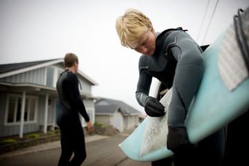 Teenage boy waxing his surfboard outside.
