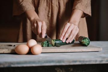 Woman slising small zucchini