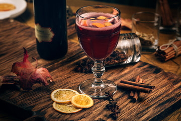 mulled red wine with spices and fruits on a wooden rustic table. Traditional hot drink at Christmas time