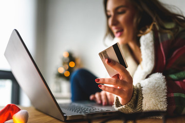 Young woman buying online at home  for winter holidays using laptop computer.