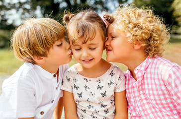 Two kids giving a little kiss to their best friend