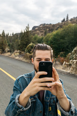 Young male taking photo with phone using electronics in outdoor nature scene