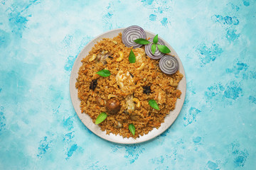 Arabic food Kabsa: chicken with rice and vegetables on a plate.