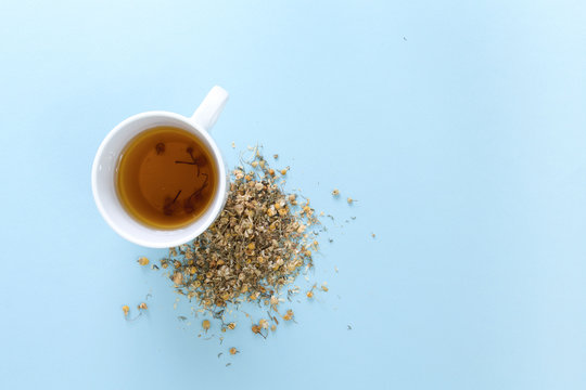 Cup of freshly brewed chamomile tea with heap of dried plant, on blue background.