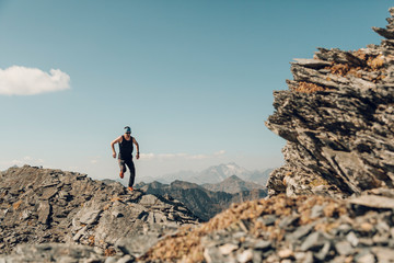 Young man running on the top of a mountain ridge