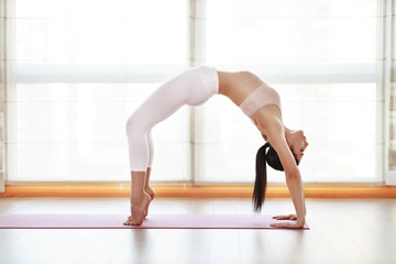 young woman practices yoga at  gym by window.