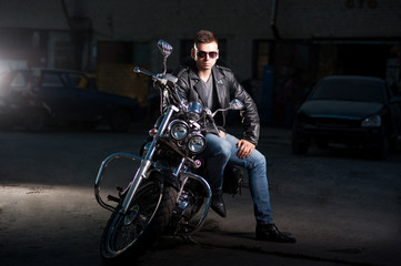 Cute biker in leather jacket sits on a motorcycle