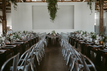 Long harvest tables with simple greenery and copper details in industrial setting for wedding