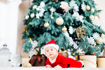 A baby in a Santa Claus suit is lying on a stomach near the Christmas tree and gifts