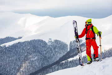 Wall Mural - A skier is standing on the slope, watching the mountain scenery